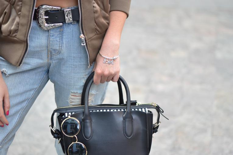 Street style outfit detail, bomber jacket, pandora bracelet, casual look, black mini bagm round glasses
