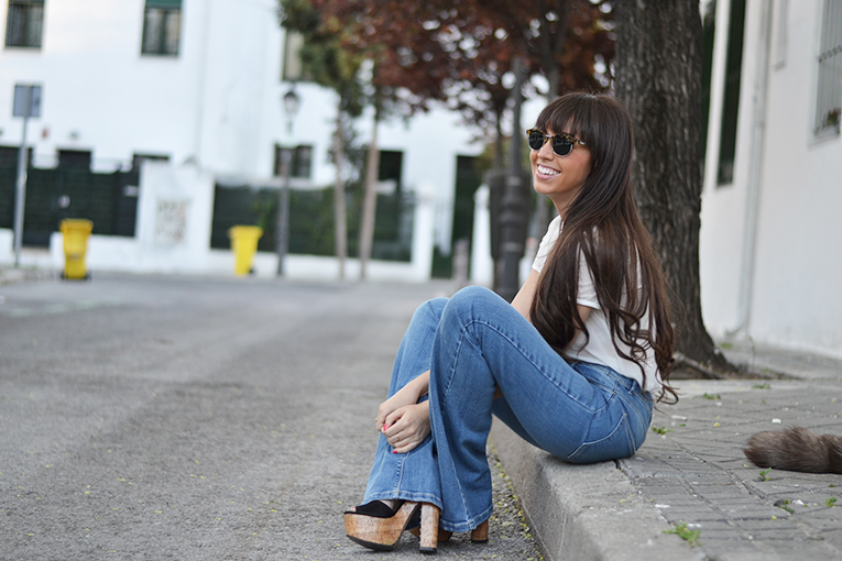 Street style outfit, flared jeans, mr boho sunglasses, vest, transparent blouse, lace bra
