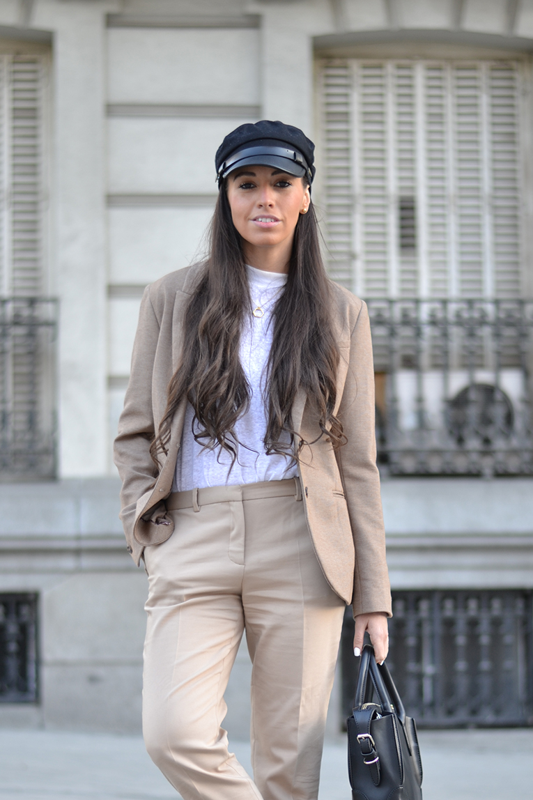 Street style, Beige set of pants and blazer, black military cap, black moccasins