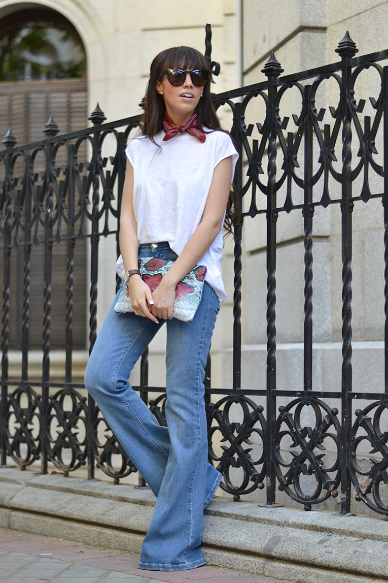Street style outfit, flared jeans, white top, burgundy dot scarf, animal print clutch, cat eye sunglasses