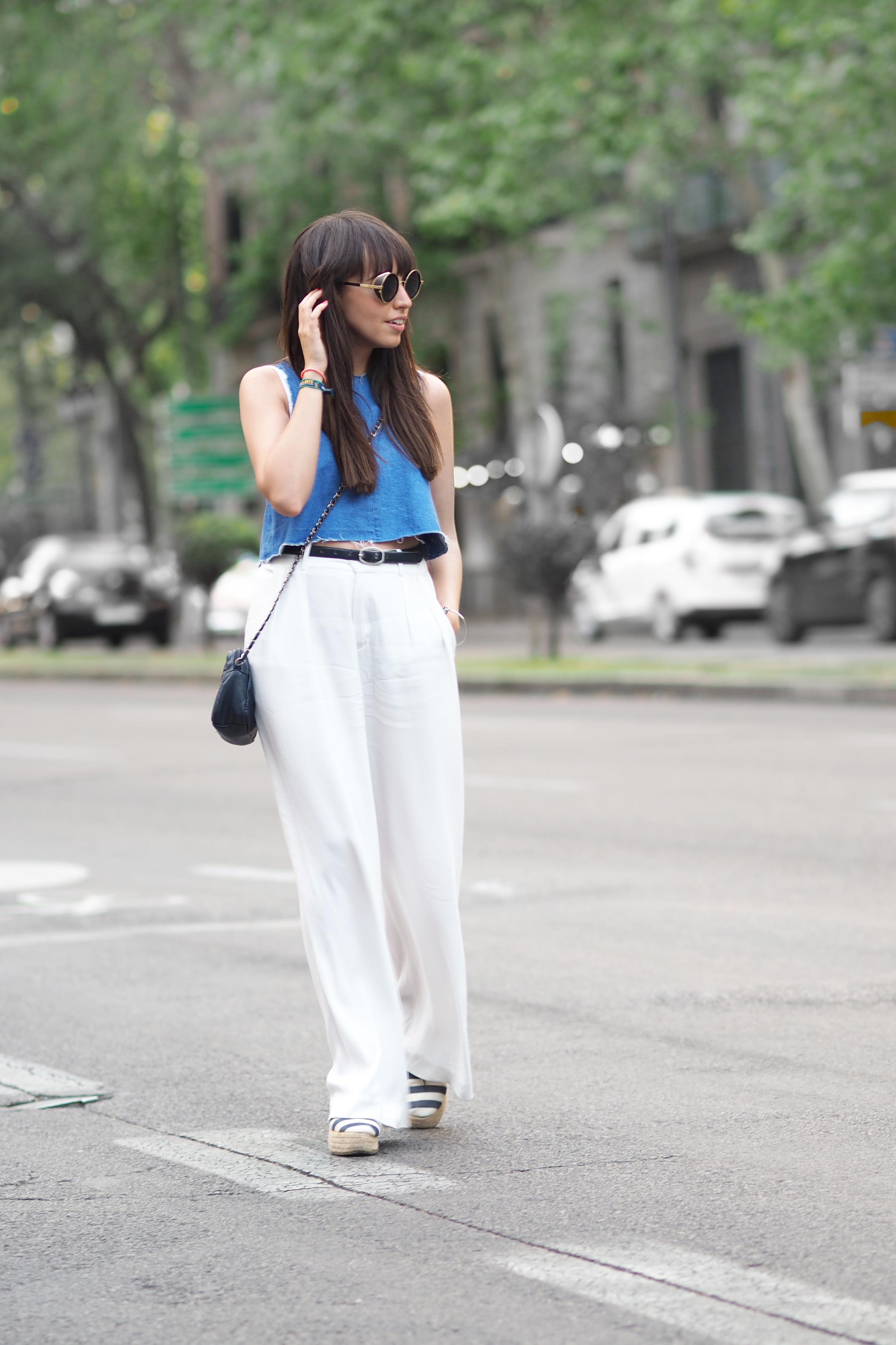 Street style, white palazzo pants, denim crop top, rounded sunglasses,
