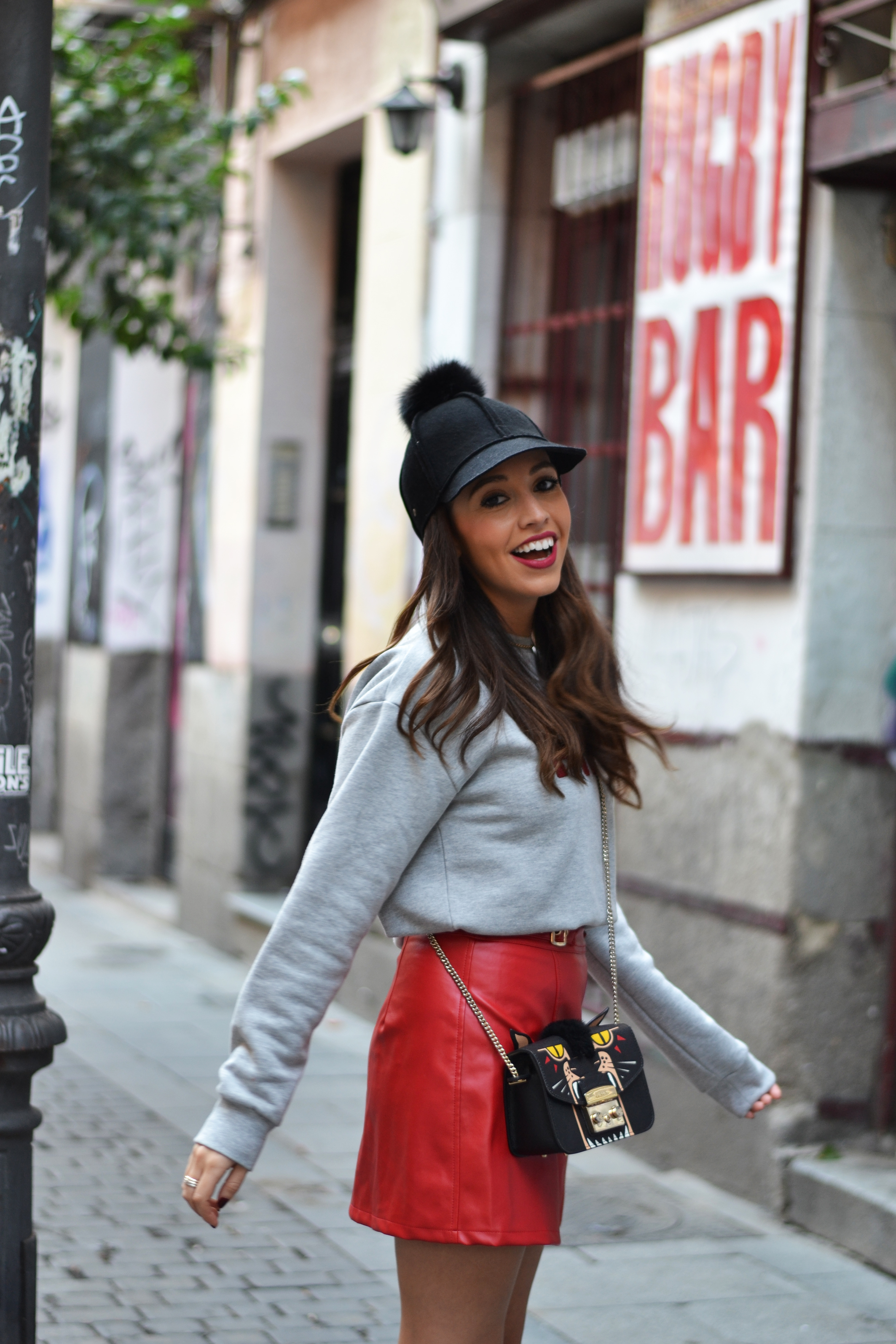 Leather red skirt, pearls boots, grey sweatshirt, pompom hat, autumn outfit